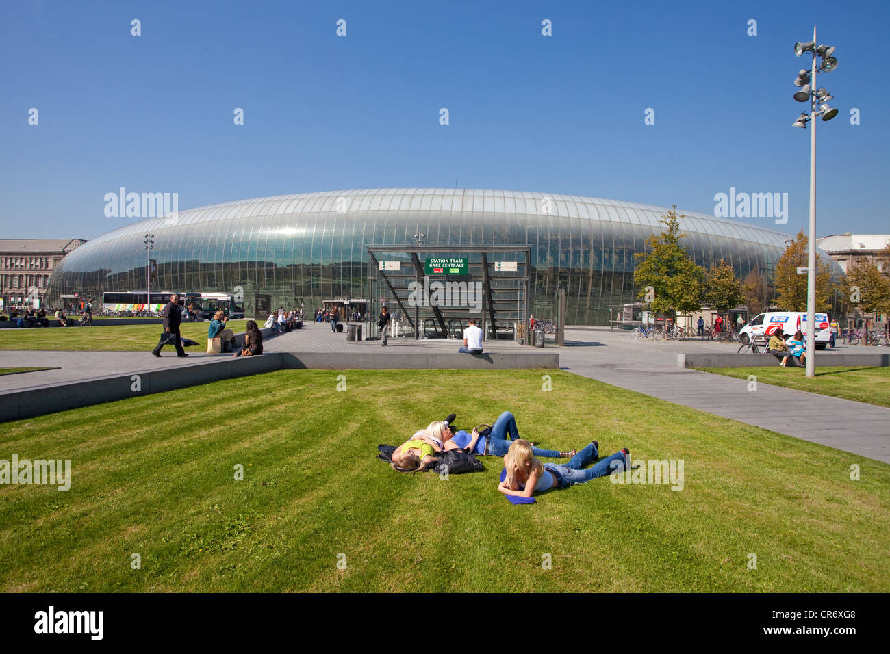 Young people lying on the lawn in front of the main train station in Strasbourg, a modern glass dome is covering - Stock Image