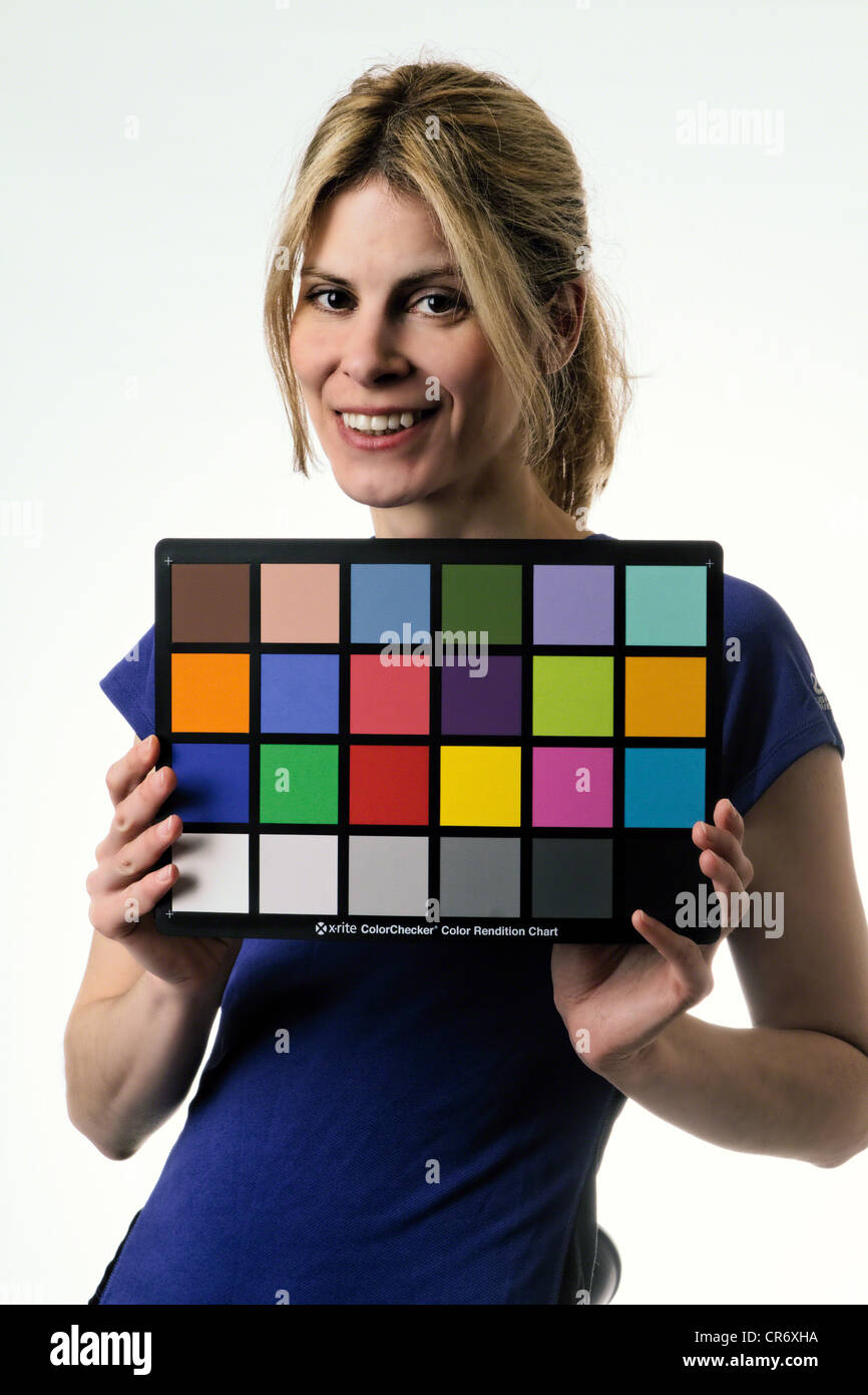 Young Model Woman Holding Color Reference Chart During Studio Shoot - Stock Image