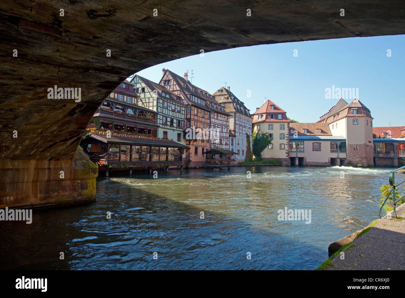 View from beneath the bridge Pont Saint-Martin, half-timber houses at the river Ille, Petite France, Strasbourg, - Stock Image