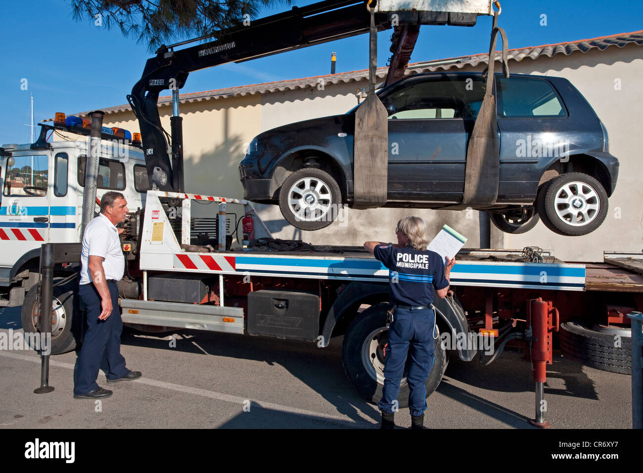 An illegally parked car being towed away, the port of St Tropez, Var, Cote d'Azur, Southern France, France, - Stock Image