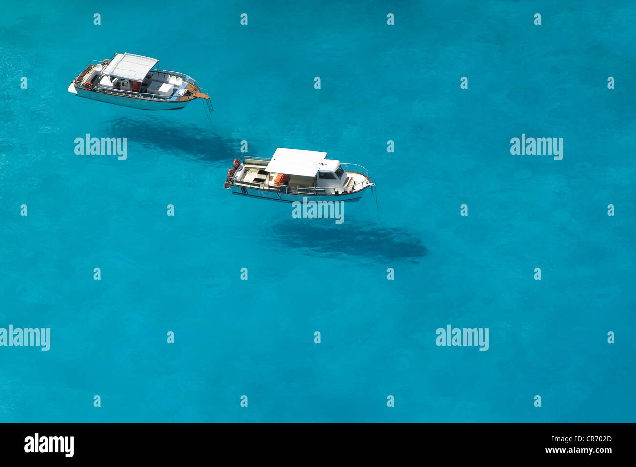 Top view of motorboats in blue, transparent waters of shipwreck bay, Zakynthos - Stock Image