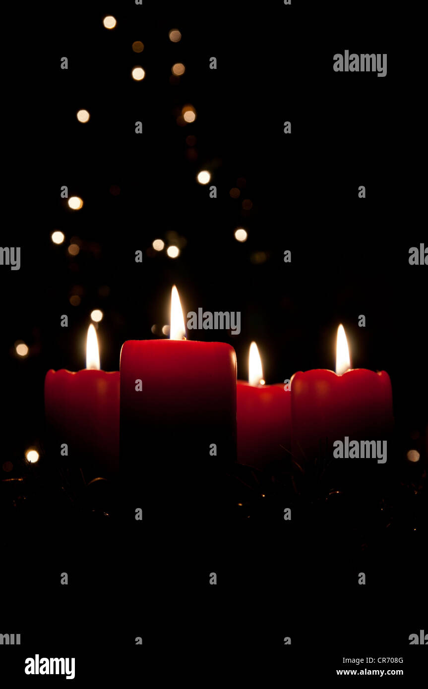 Christmas advent wreath with red burning candles. Lights on x-mas tree in background - Stock Image