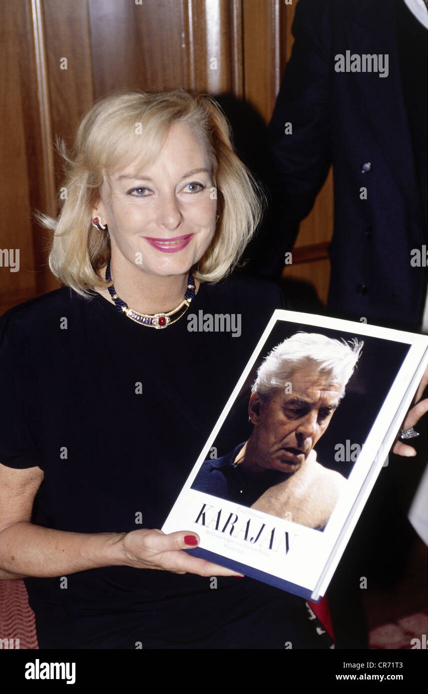 Karajan, Herbert von, 5.4.1908 - 16.7.1989, Austrian conductor, his wife, half length, holding a book about her Stock Photo