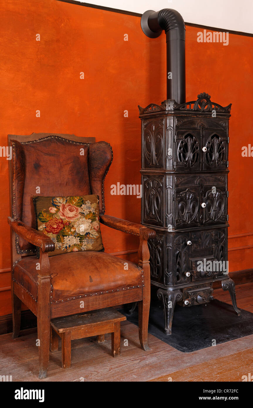 Fauteuil chair and cast-iron stove, 1900, living room in the teacher's apartment, school building from Pfaffenhofen - Stock Image