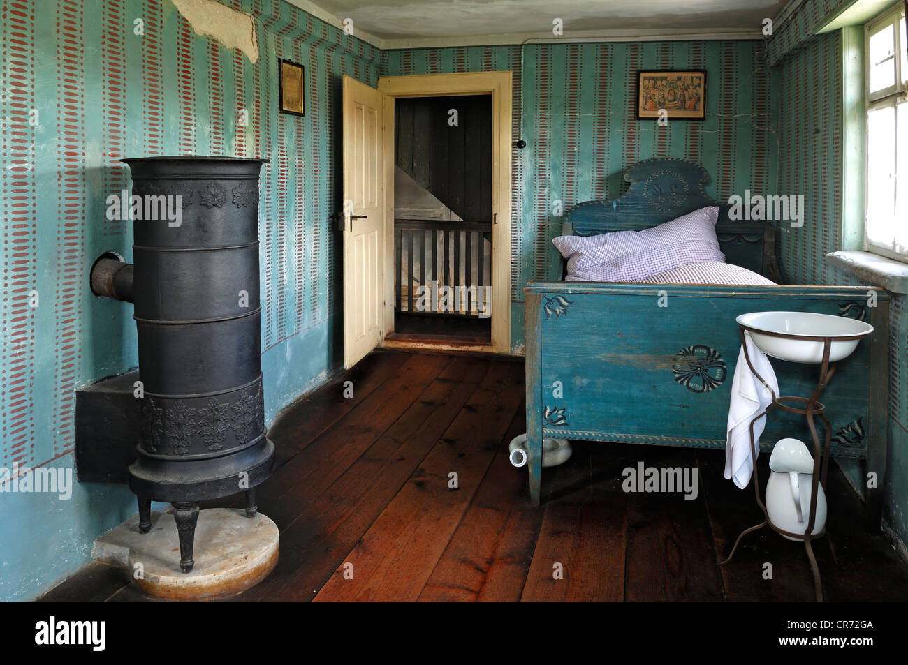 Retiree's room with stove and bed, 1911, farmhouse from Herrnbechtheim, Franconian open-air museum, Eisweiherweg - Stock Image