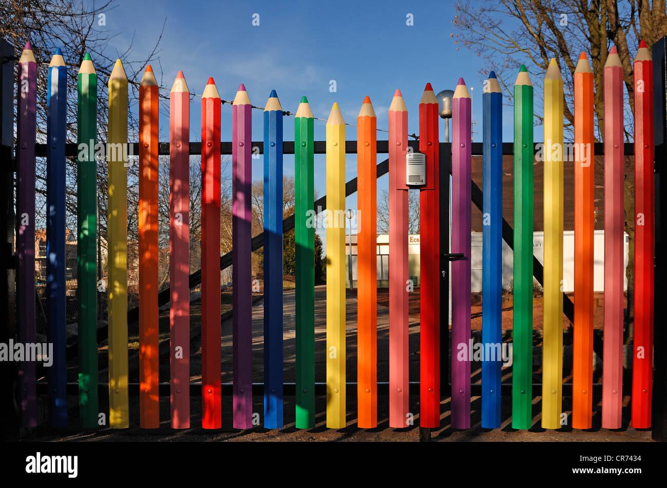 Large coloured pencils forming the gate of the A. Mozart School, Rue de l'Hôtel de Ville, Marckolsheim, - Stock Image