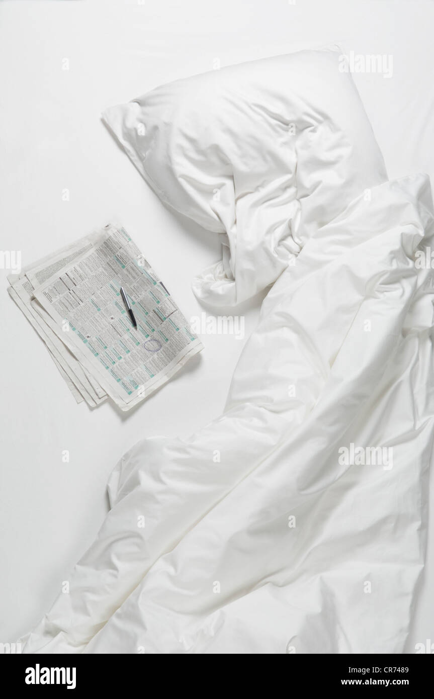 Newspaper with pen on bed - Stock Image