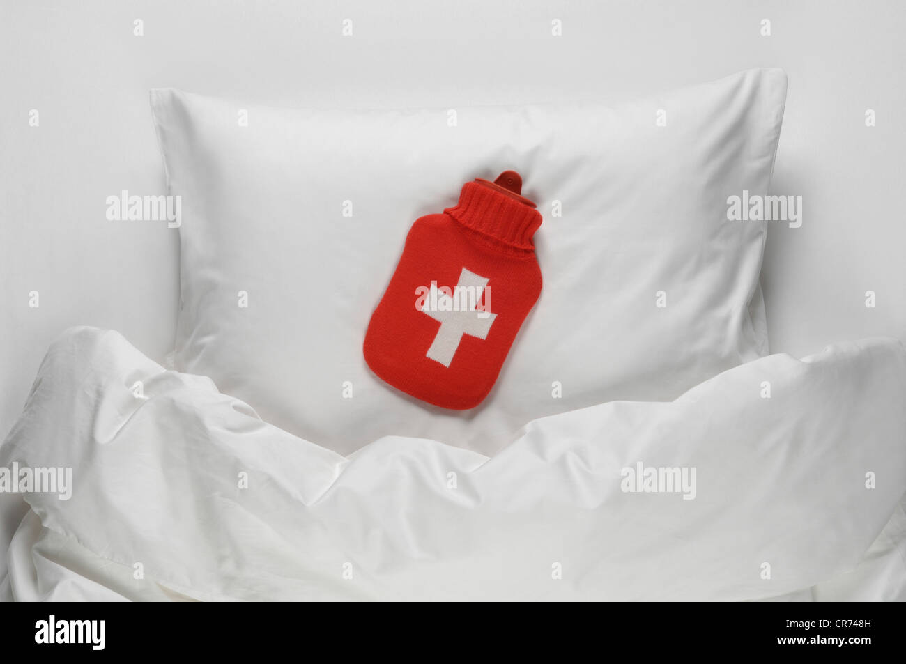 Hot water bottle on bed - Stock Image