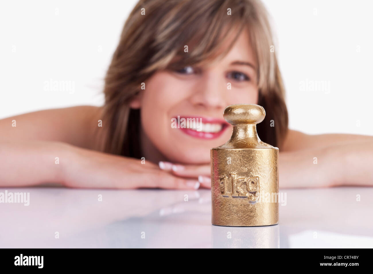 Young woman with 1 kg weight, smiling, portrait - Stock Image