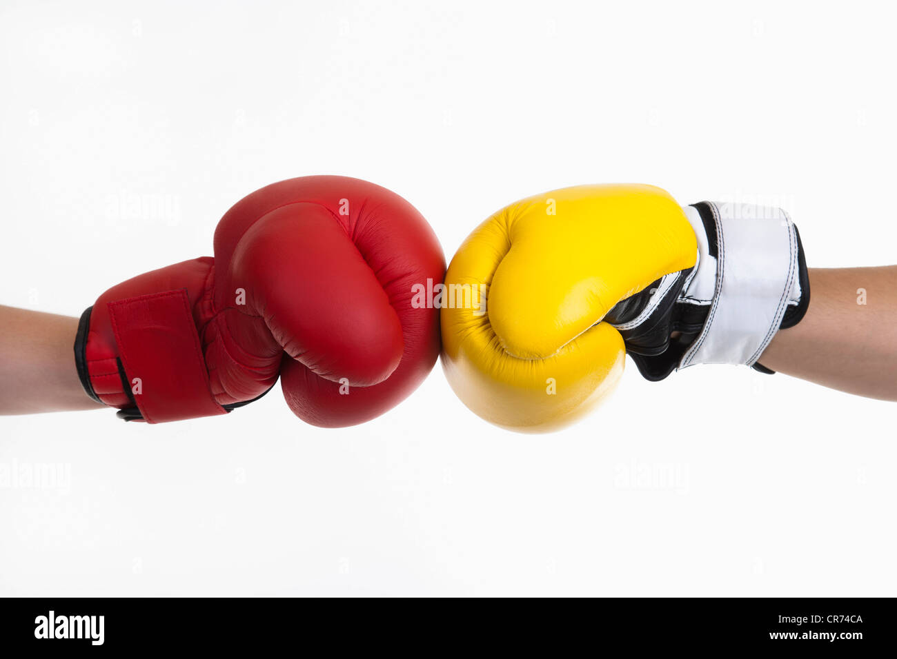 Human hands with red and yellow boxing gloves - Stock Image