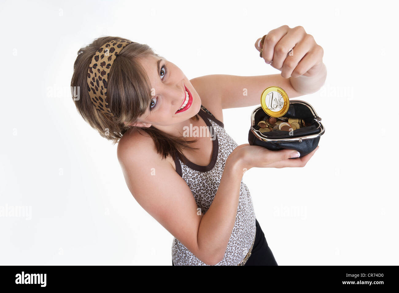 Young woman holding wallet with one euro coin, smiling, portrait - Stock Image