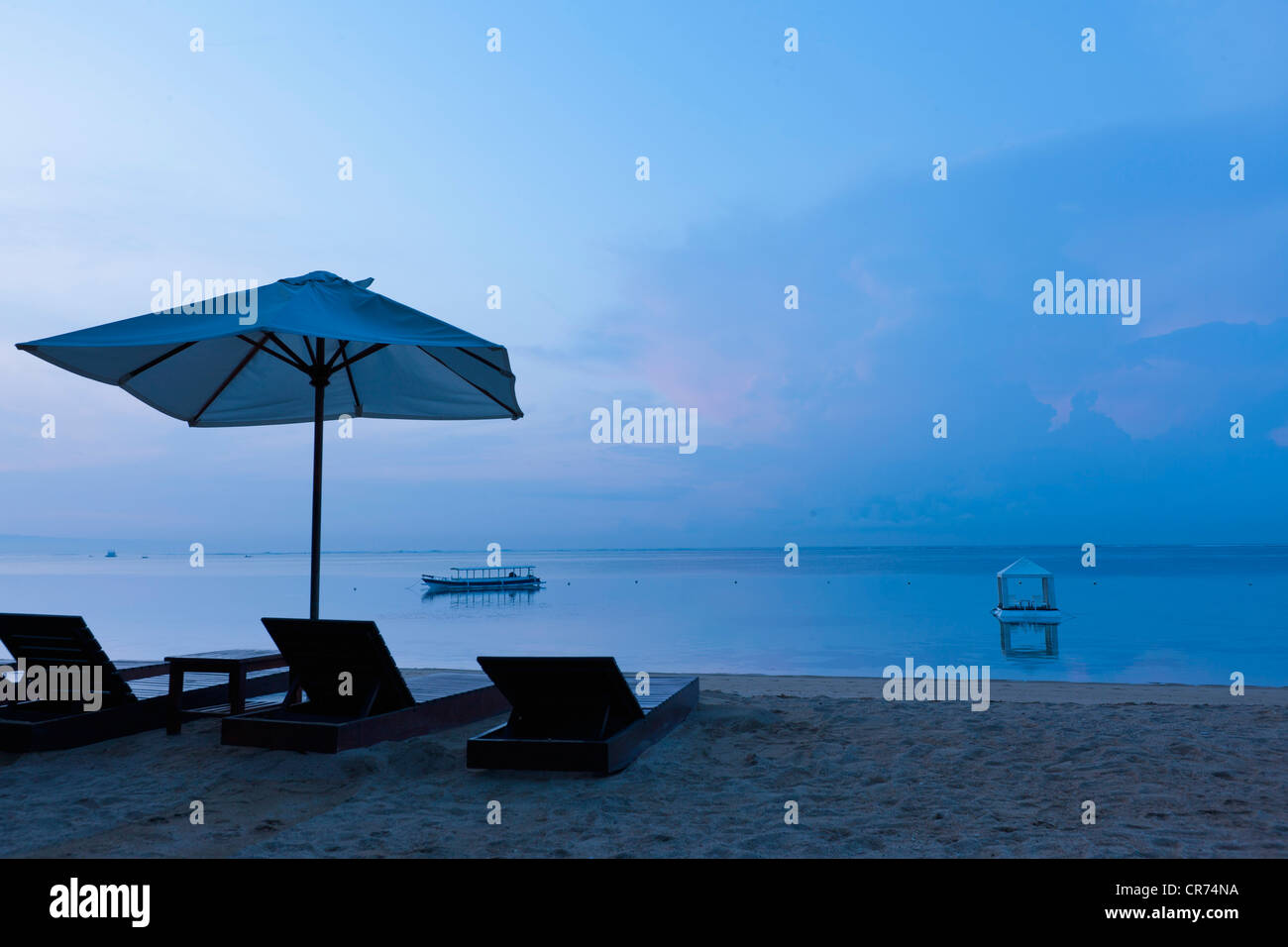 Indonesia, Bali, Sanur, Sun loungers and sunshade on beach - Stock Image
