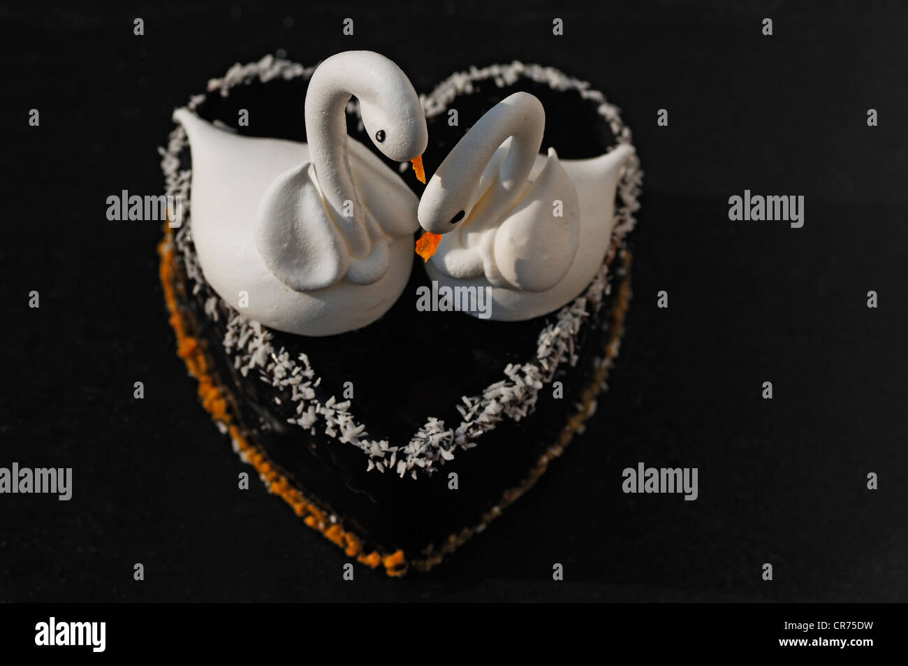 Two meringue swans on a chocolate heart, beaks made from apricots, on a slate in a patisserie - Stock Image