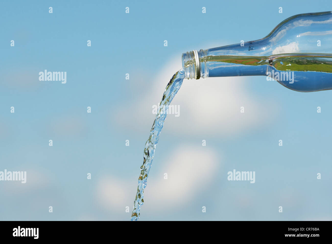 Pouring drinking water from a glass bottle against a blue sky - Stock Image