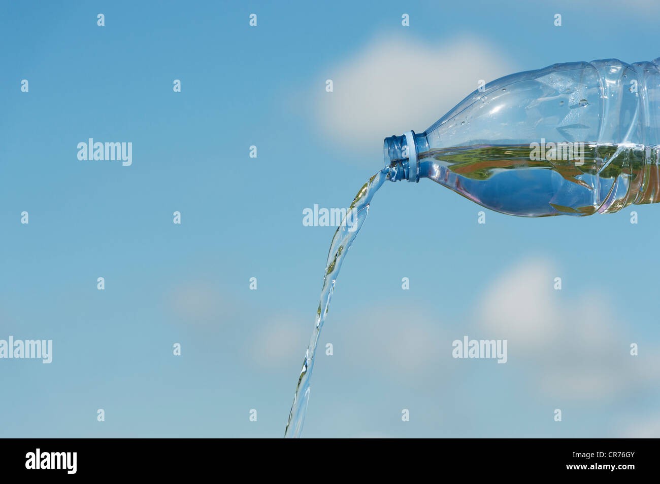 Pouring drinking water from a plastic bottle against a blue sky - Stock Image