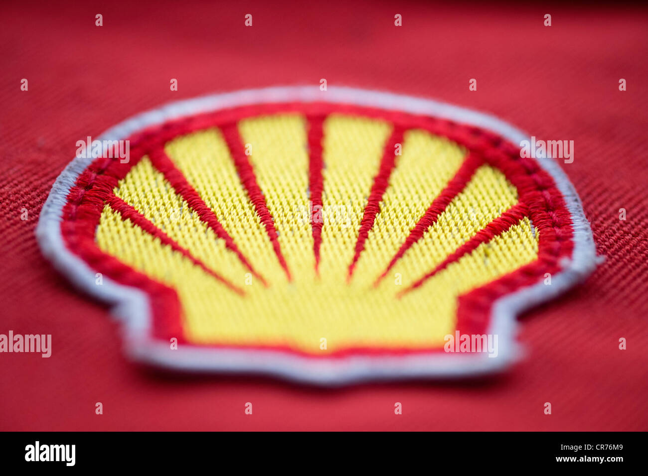 Detail of cloth logo patch on safety overalls of worker for Royal Dutch Shell oil company. - Stock Image