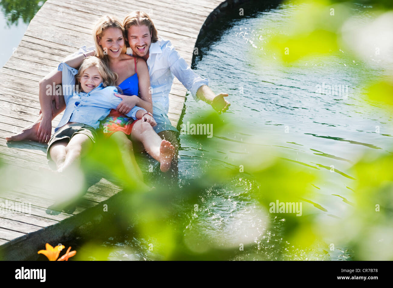 Austria, Salzburg County, Family sitting on bridge over natural pool Stock Photo