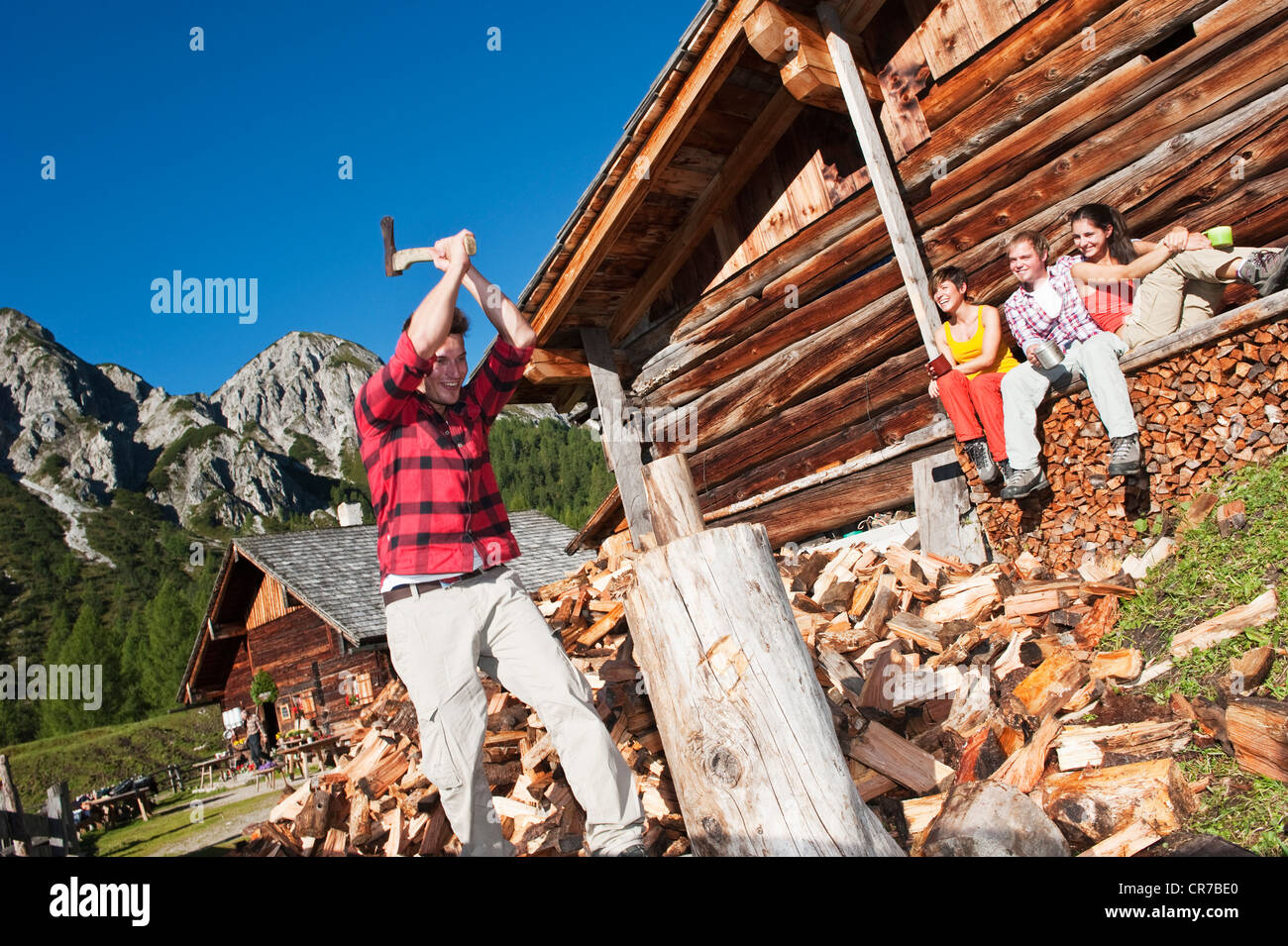 Austria, Salzburg County, Friends looking at man chopping wood near alpine hut Stock Photo