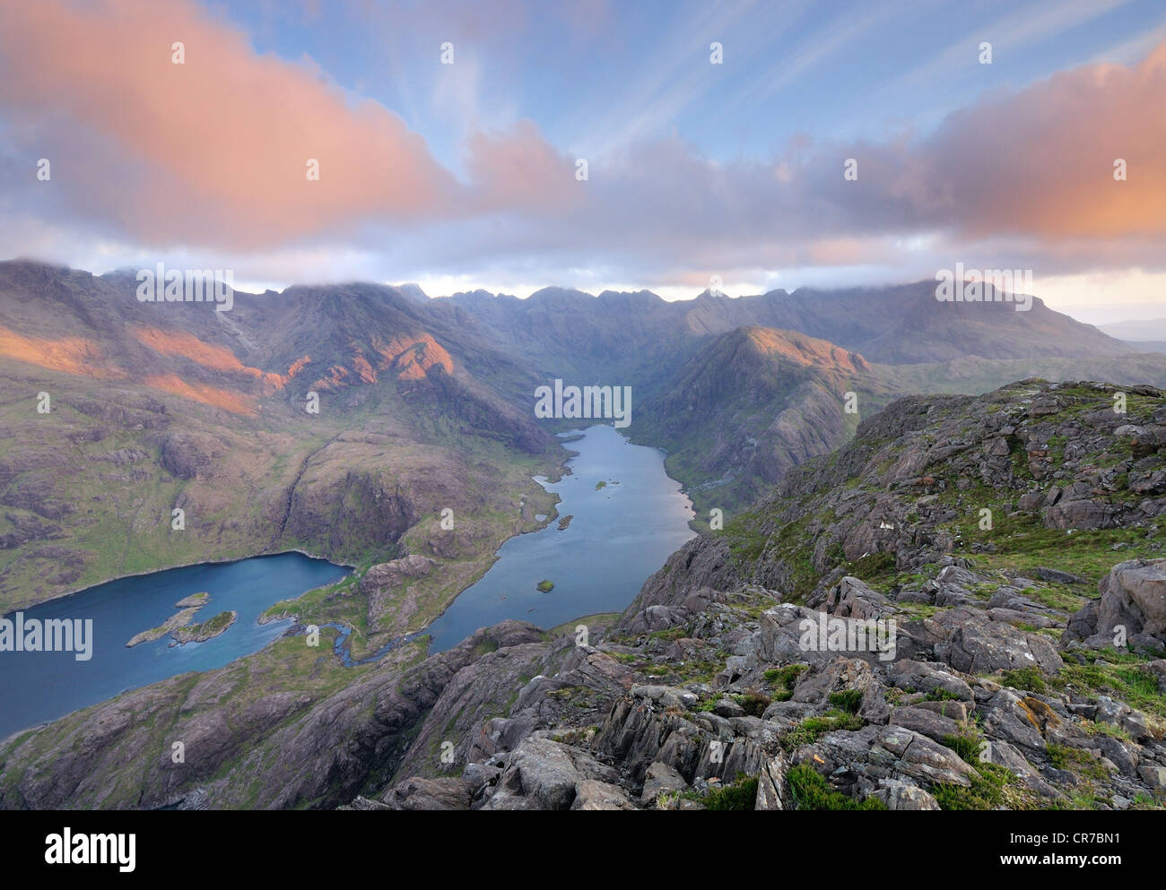 Pink sunlight and clouds over Loch Coruisk and the jagged peaks of the Black Cuillin mountain range on the Isle Stock Photo