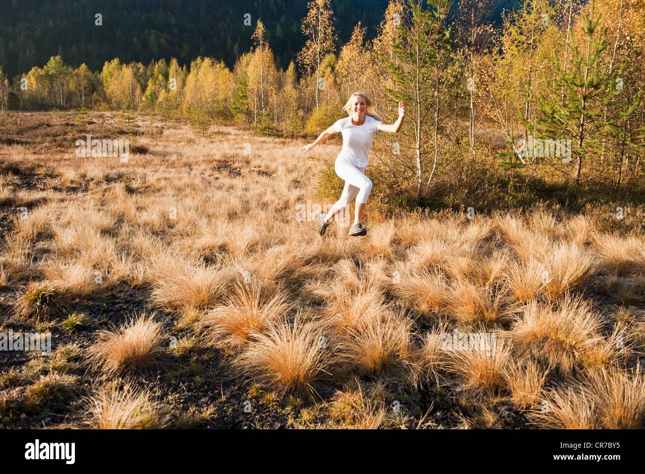 Austria, Salzburg, Young woman running in autumn Stock Photo
