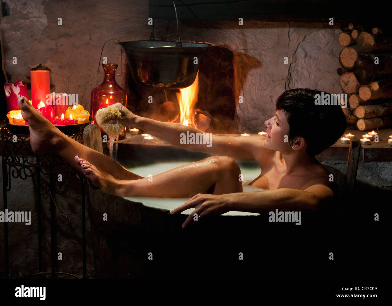 Austria, Salzburg County, Young woman taking bath in wooden tub - Stock Image