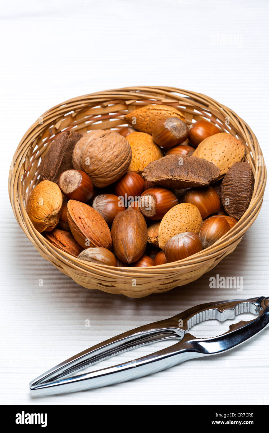 Mixed nuts in basket with nut cracker on light background - Stock Image
