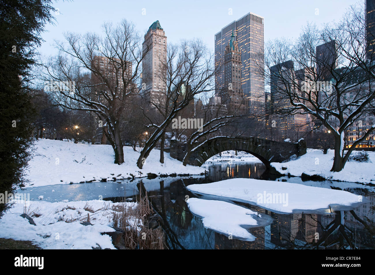 United States, New York City, Manhattan, Central Park in winter under the snow, The Pond, Gapstow Bridge and the - Stock Image