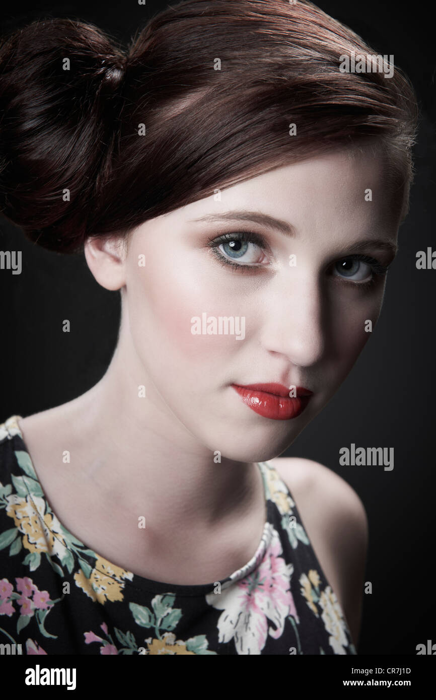 Vintage style portrait of model with red hair tied in a bun - Stock Image