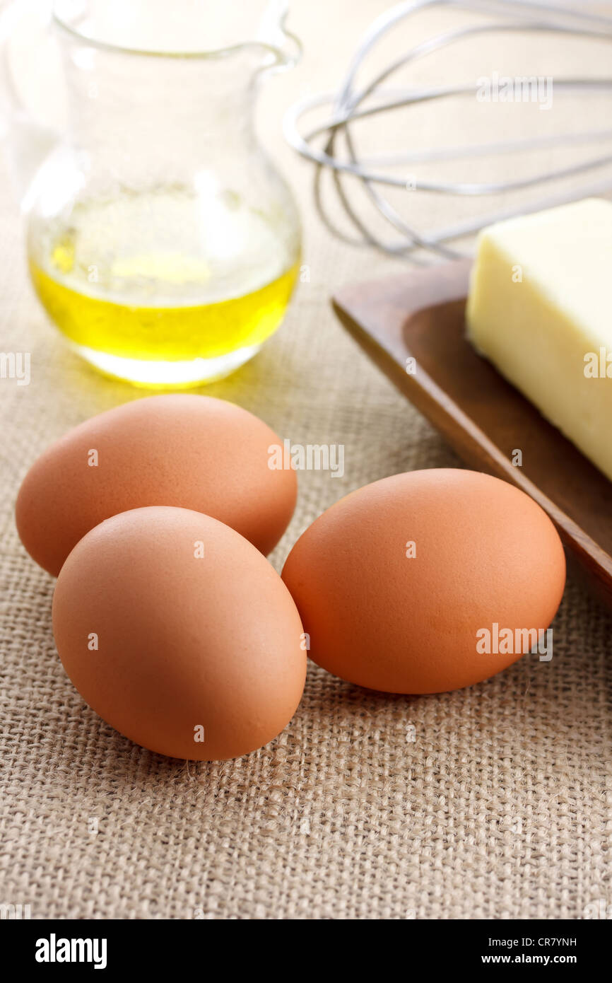 Eggs with oil butter and whisk - Stock Image