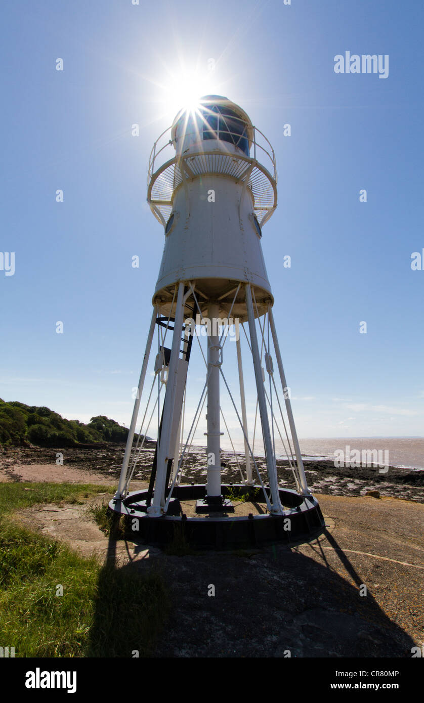 Black Nore Lighthouse in Somerset with sunflare being used as lightsource. - Stock Image