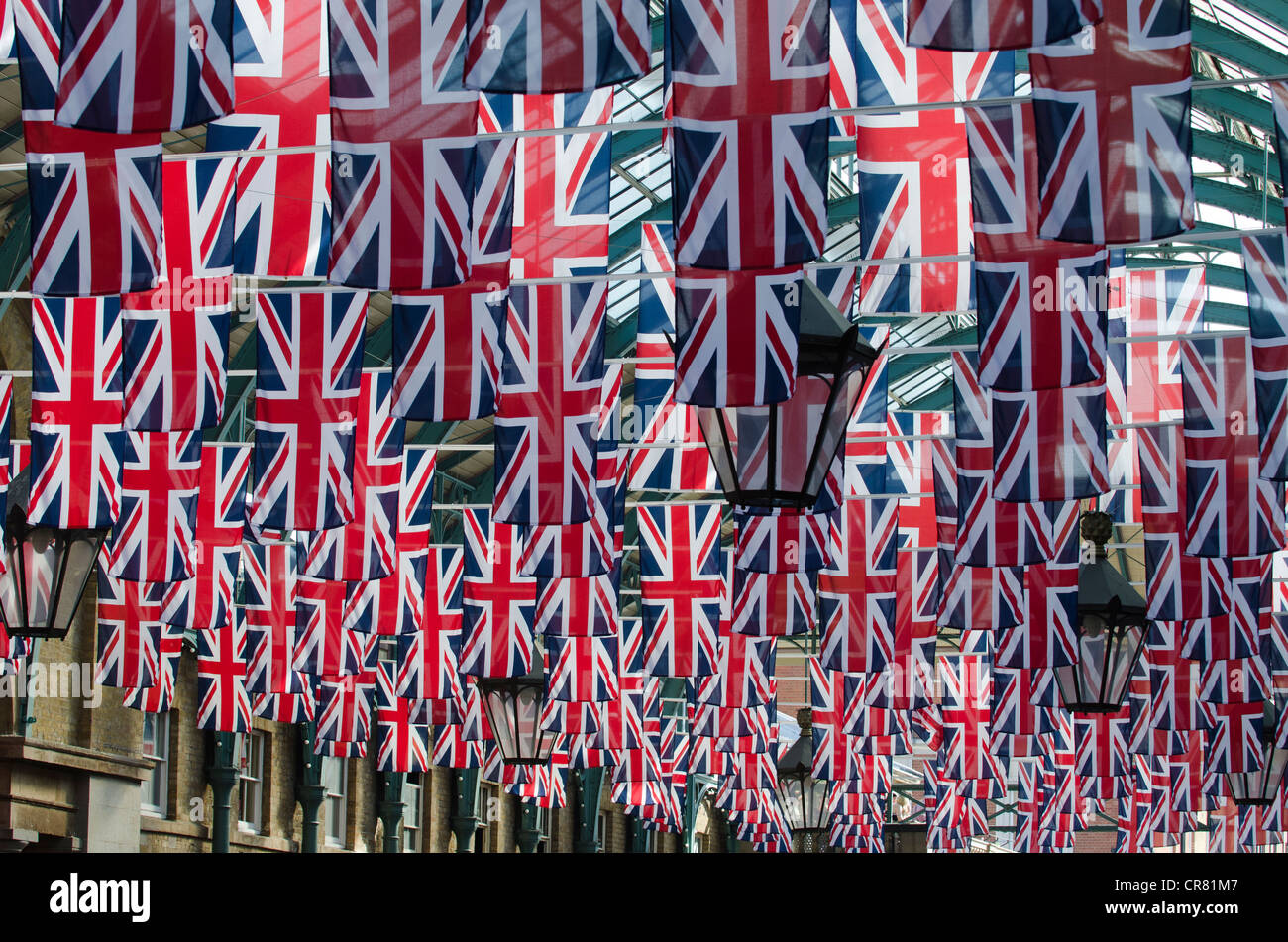 Union Flags hanging from Covent Garden covered market Westminster, London Uk - Stock Image