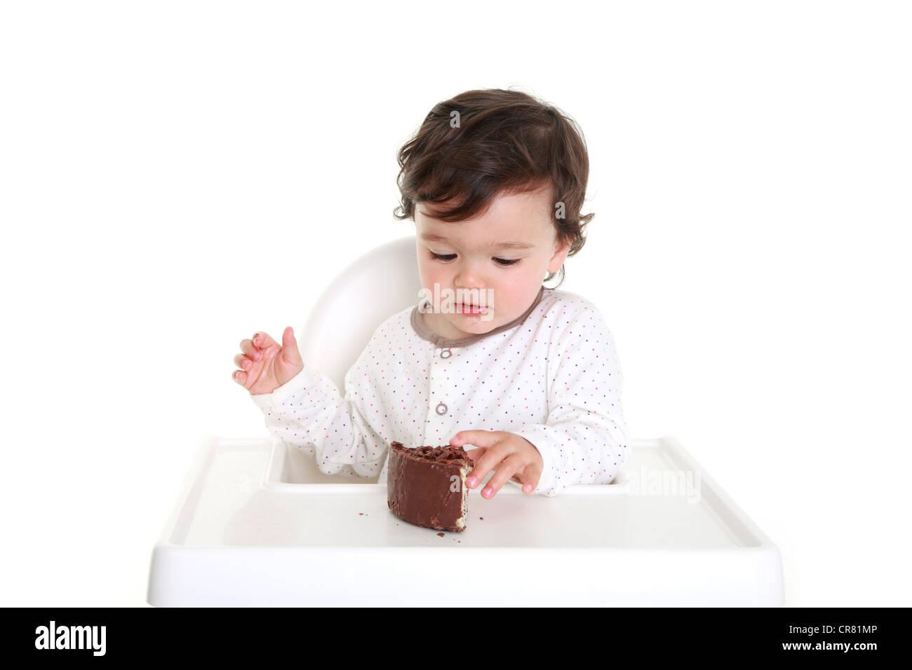 Baby eating chocolate cake - Stock Image