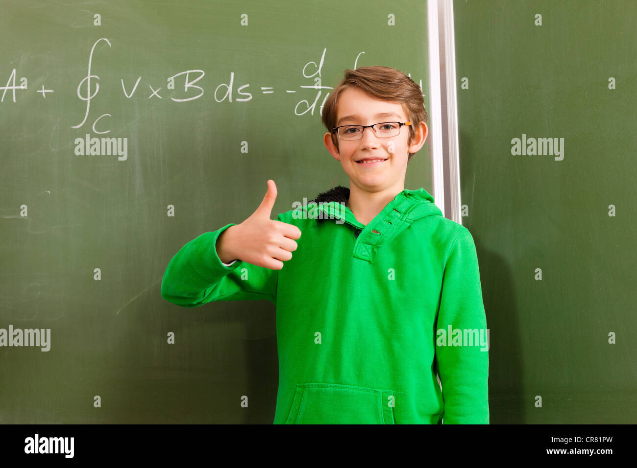 Education - Child or pupil at blackboard in school in math, the kid is very intelligent for it calculates difficult - Stock Image