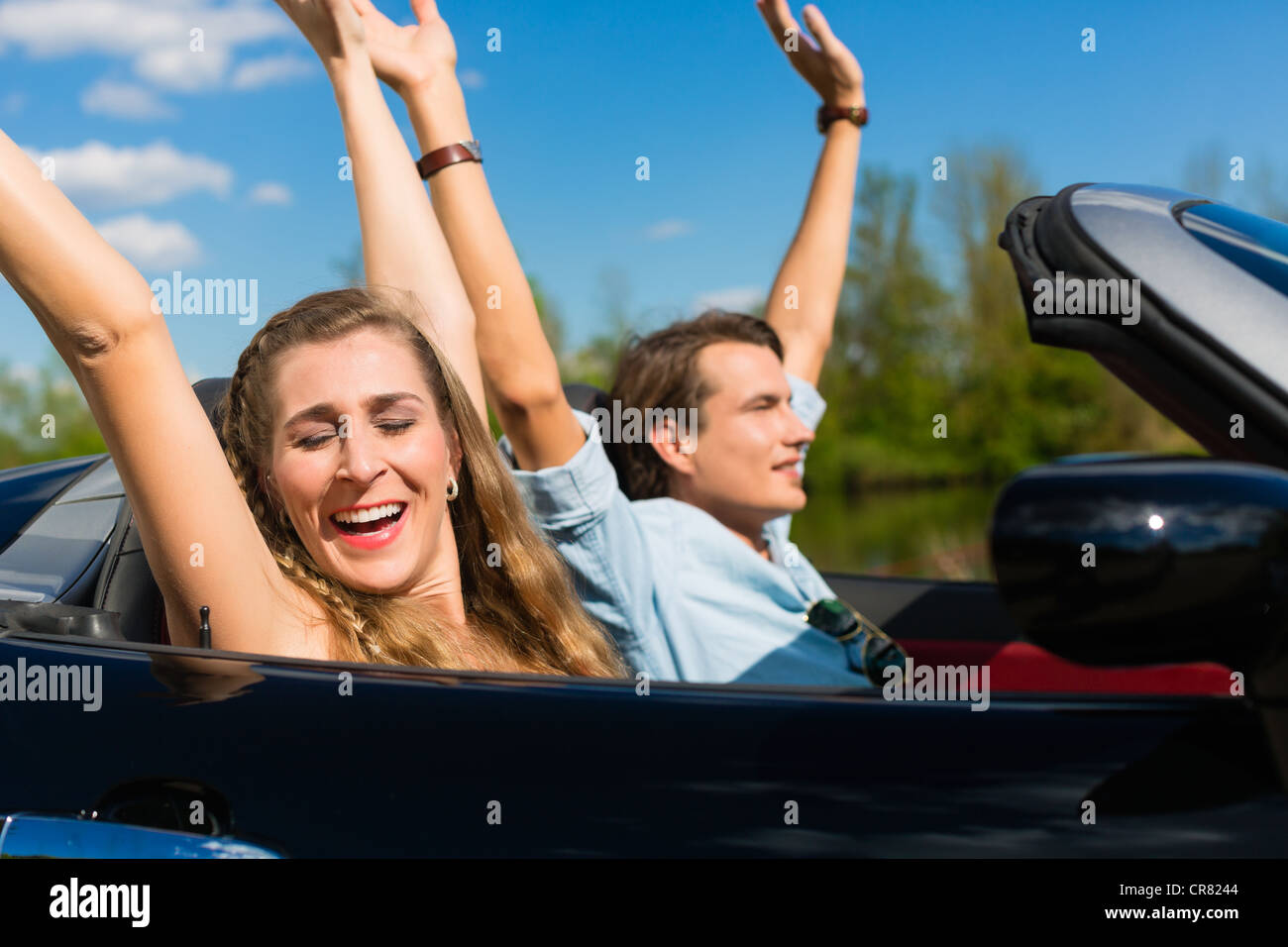 Young hip couple - man and woman - with cabriolet convertible car in summer on a day trip - Stock Image