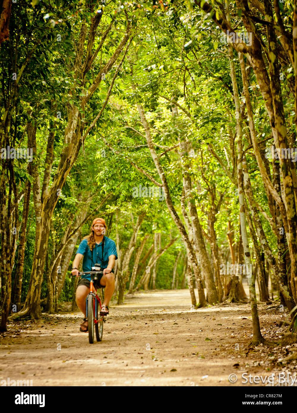 Tourist enjoys the bike ride on the 'sacbe' (white road) to the Coba Maya Ruins, Yucatan Penisula, Quintana - Stock Image