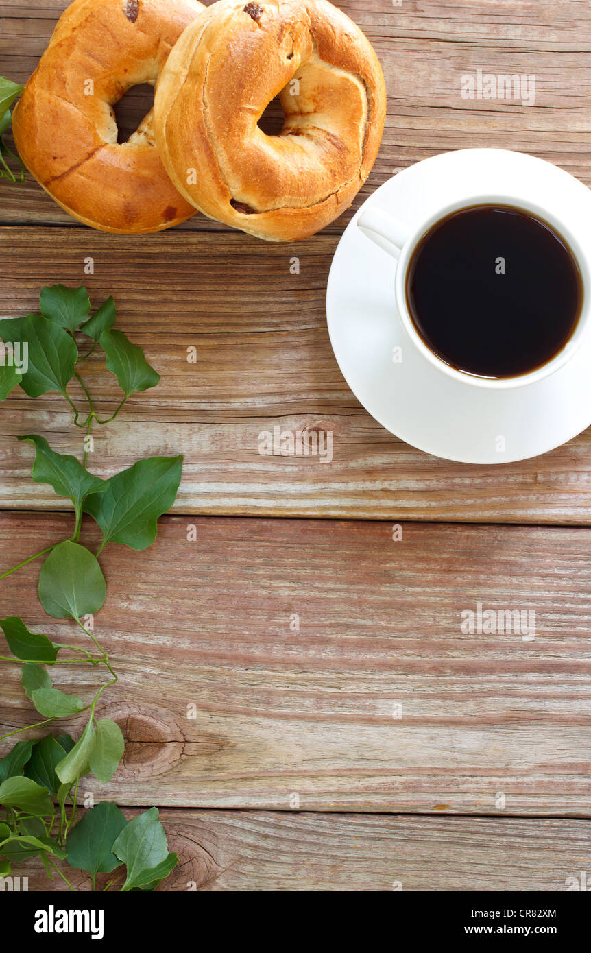 fresh cup of hot coffee with bagels on rustic wood slaps with copyspace - Stock Image