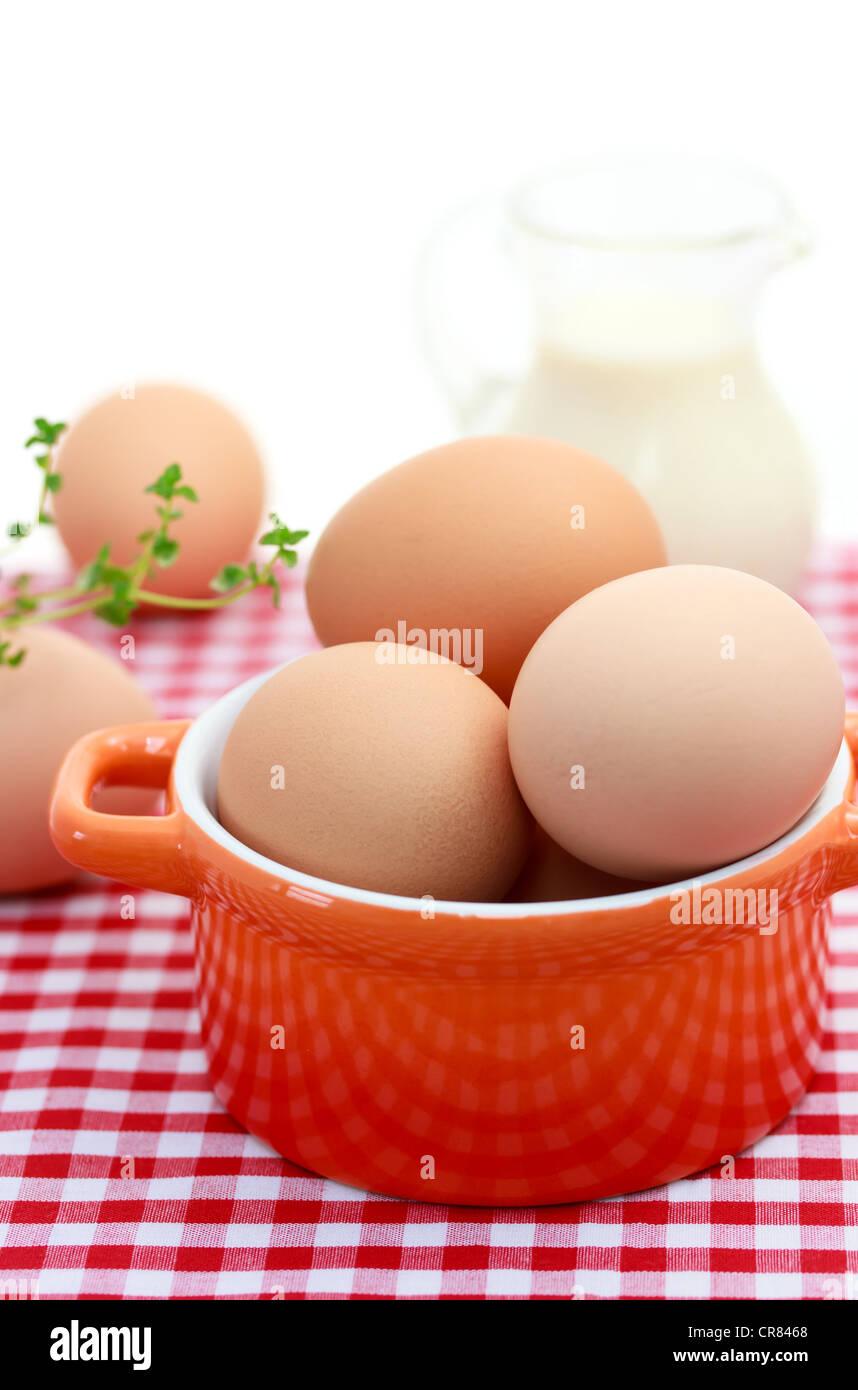 Fresh Eggs in Red Ceramic Pot Stock Photo