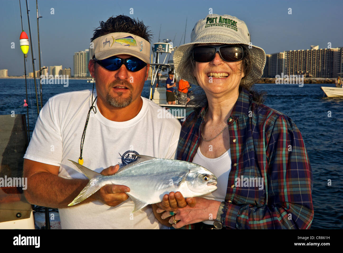 Sport fishing guide female angler holding pompano inshore saltwater game fish Perdido Pass - Stock Image