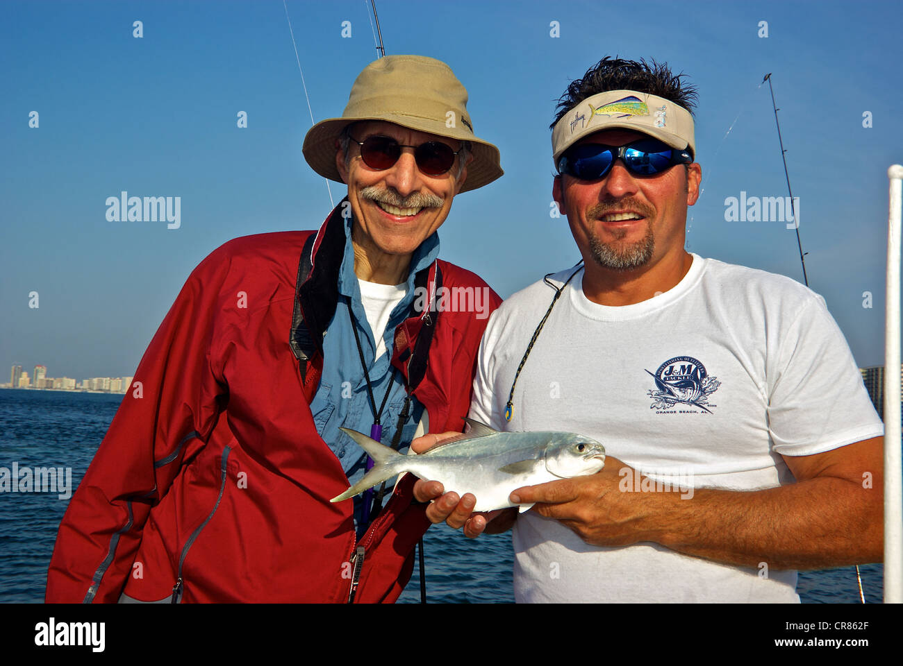 Sport fishing guide holding pompano inshore saltwater game fish male angler Perdido Pass - Stock Image