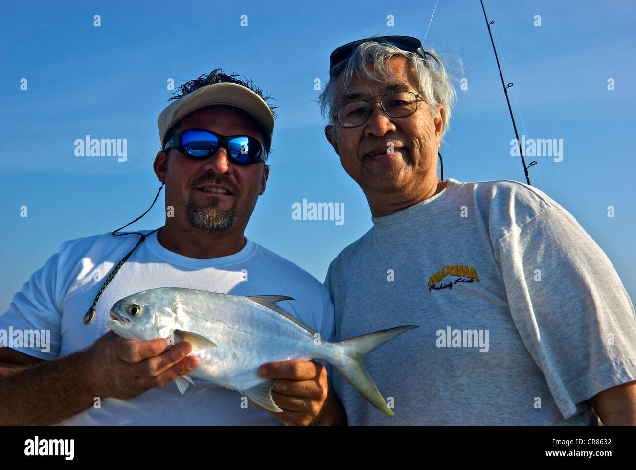 Sport fishing guide holding pompano inshore saltwater game fish Asian male angler Perdido Pass - Stock Image