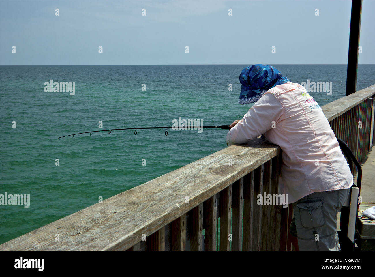 Female angler leaning on wide wooden railing Gulf Shores State Park Alabama sport fishing pier hazy overcast Stock Photo