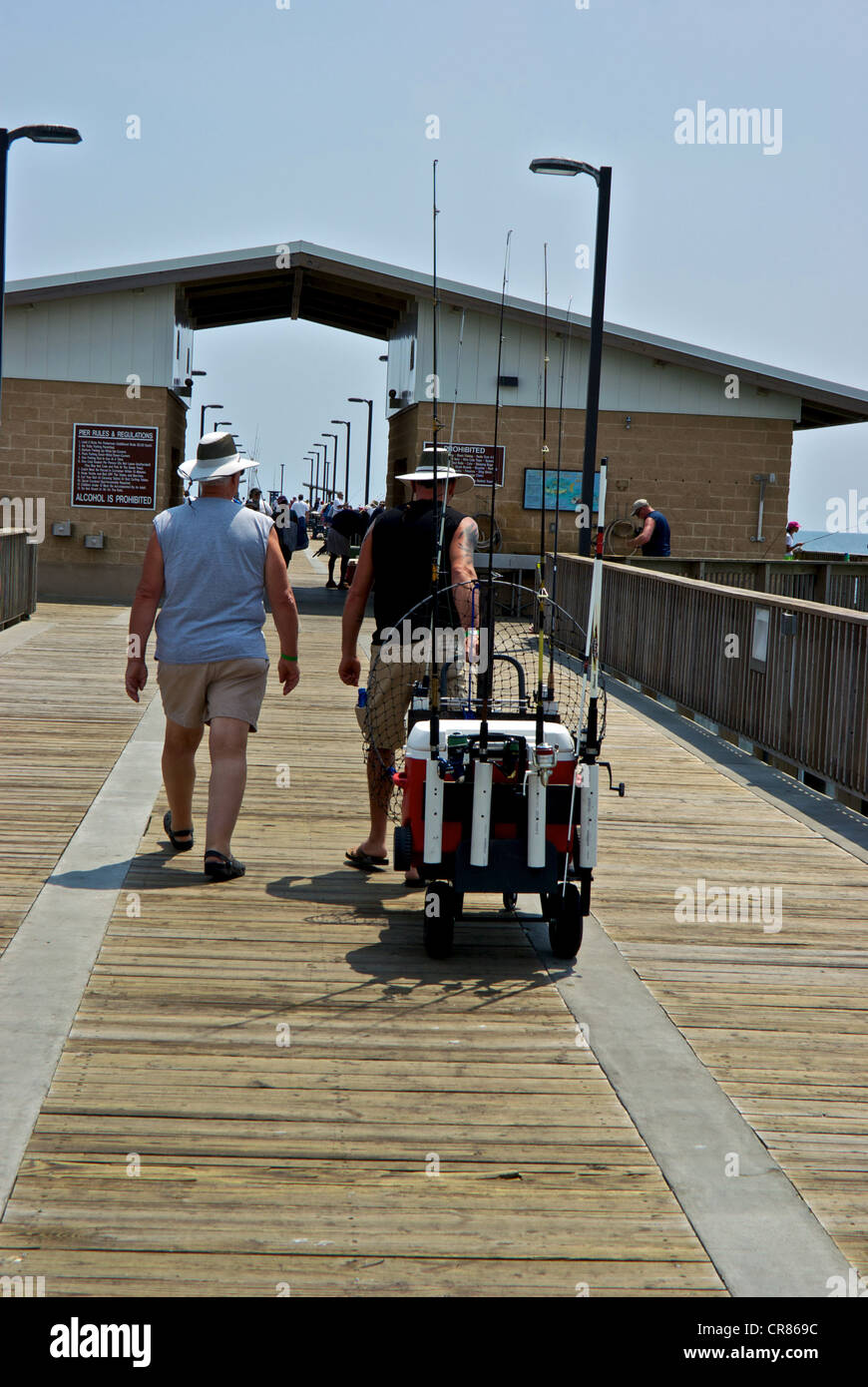 Anglers towing fishing tackle cart Gulf Shores State Park Alabama sport angling pier boardwalk Stock Photo