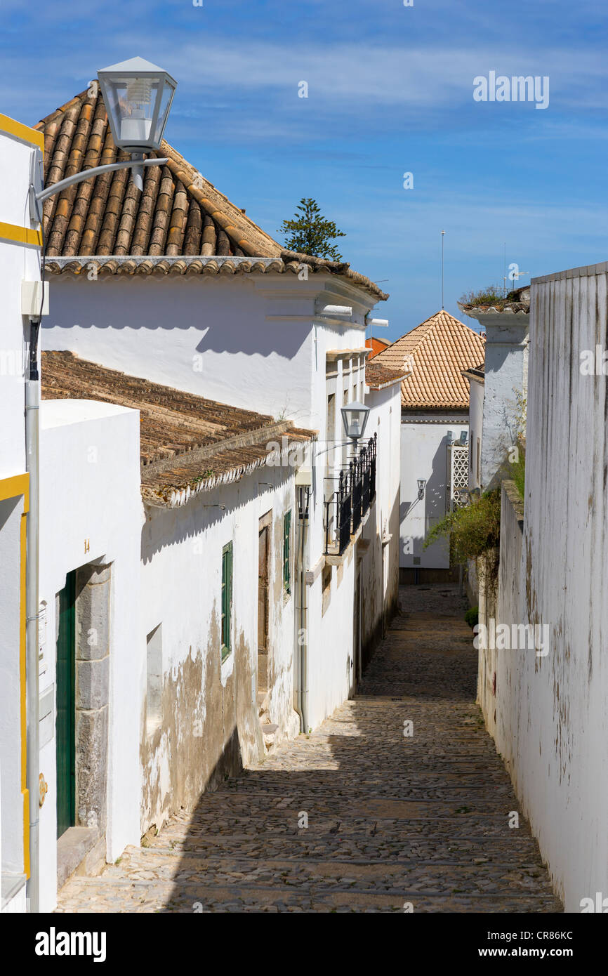 Narrow cobbled street in the Old Town, Tavira, Algarve, Portugal - Stock Image
