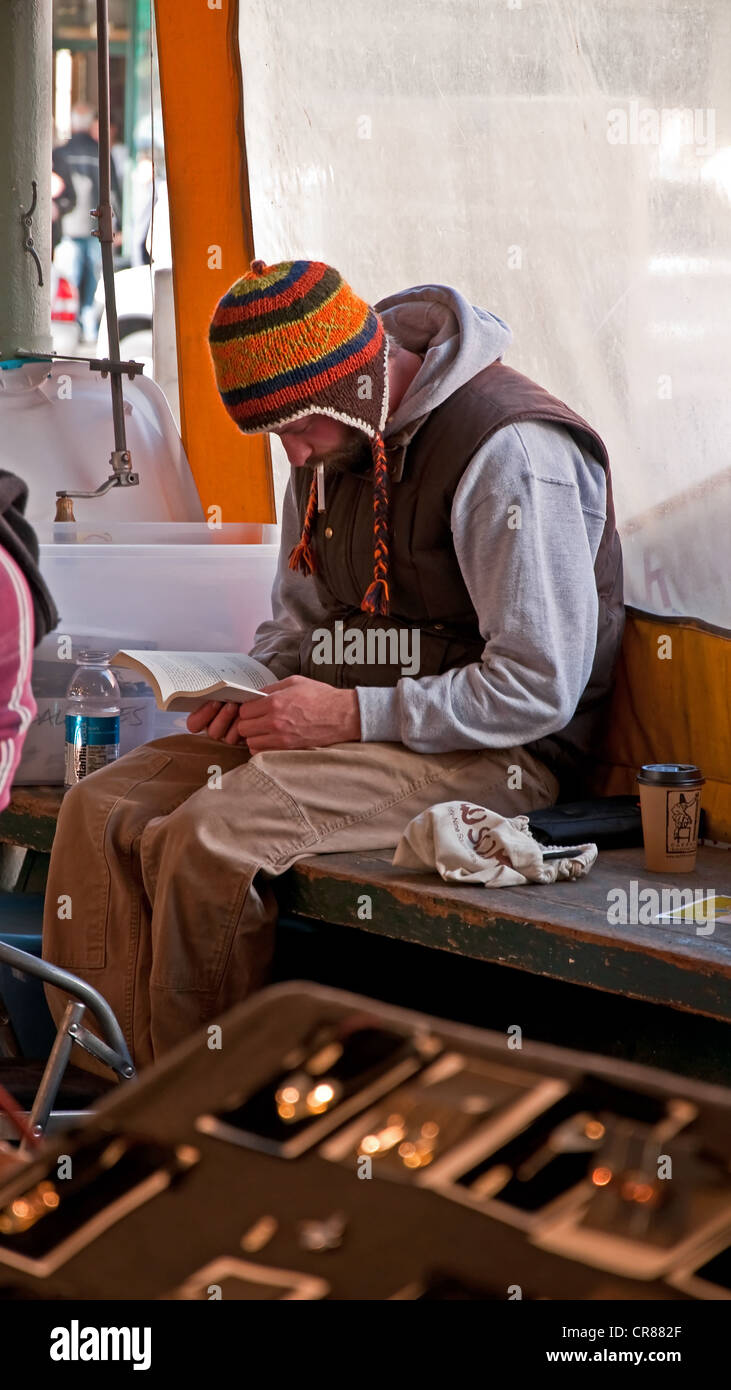 This earthy, natural looking guy wearing a hat and colder weather clothing is reading a book in an outdoor market. - Stock Image
