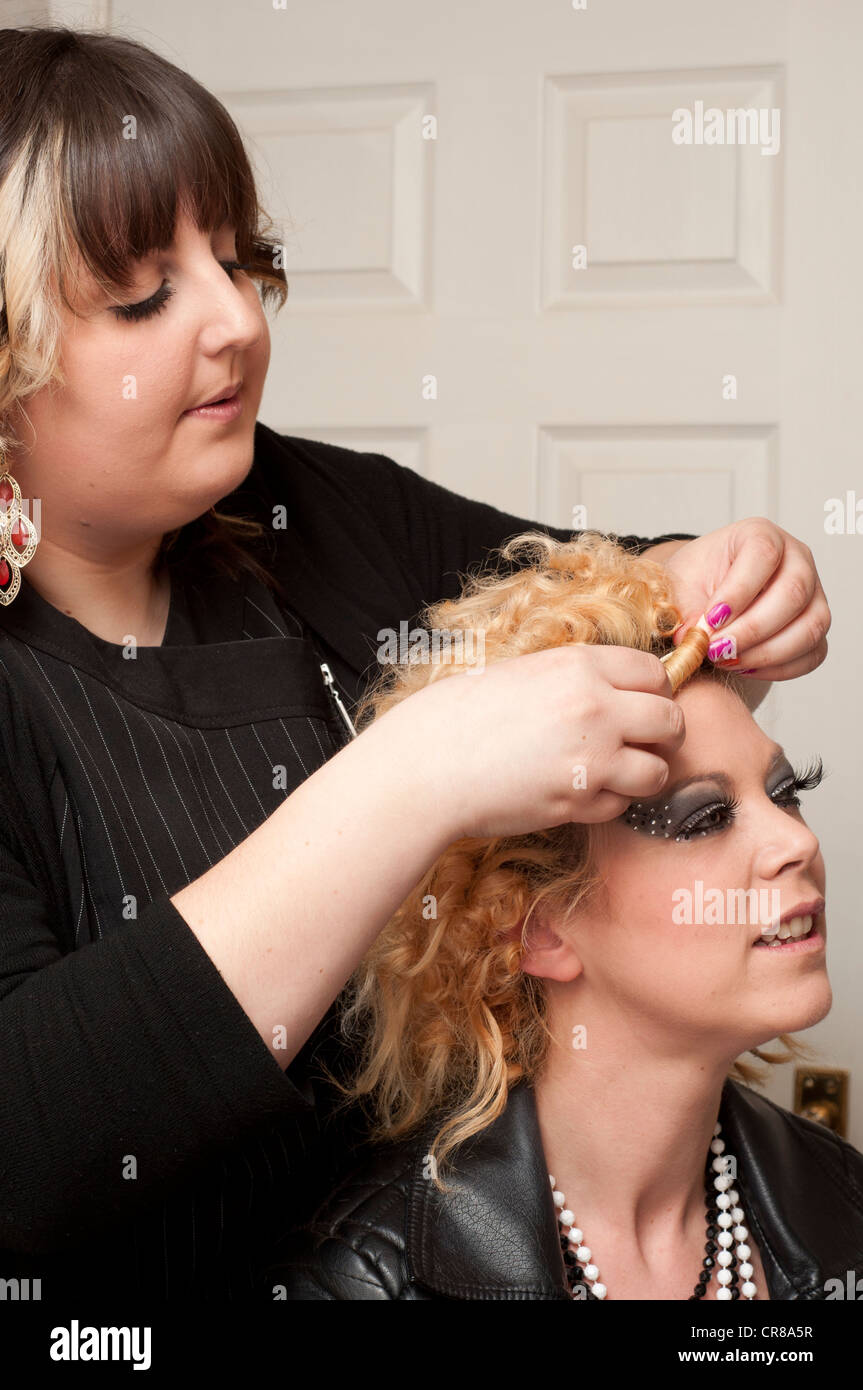 Mobile hair dresser using a hair dryer while styling hair. - Stock Image