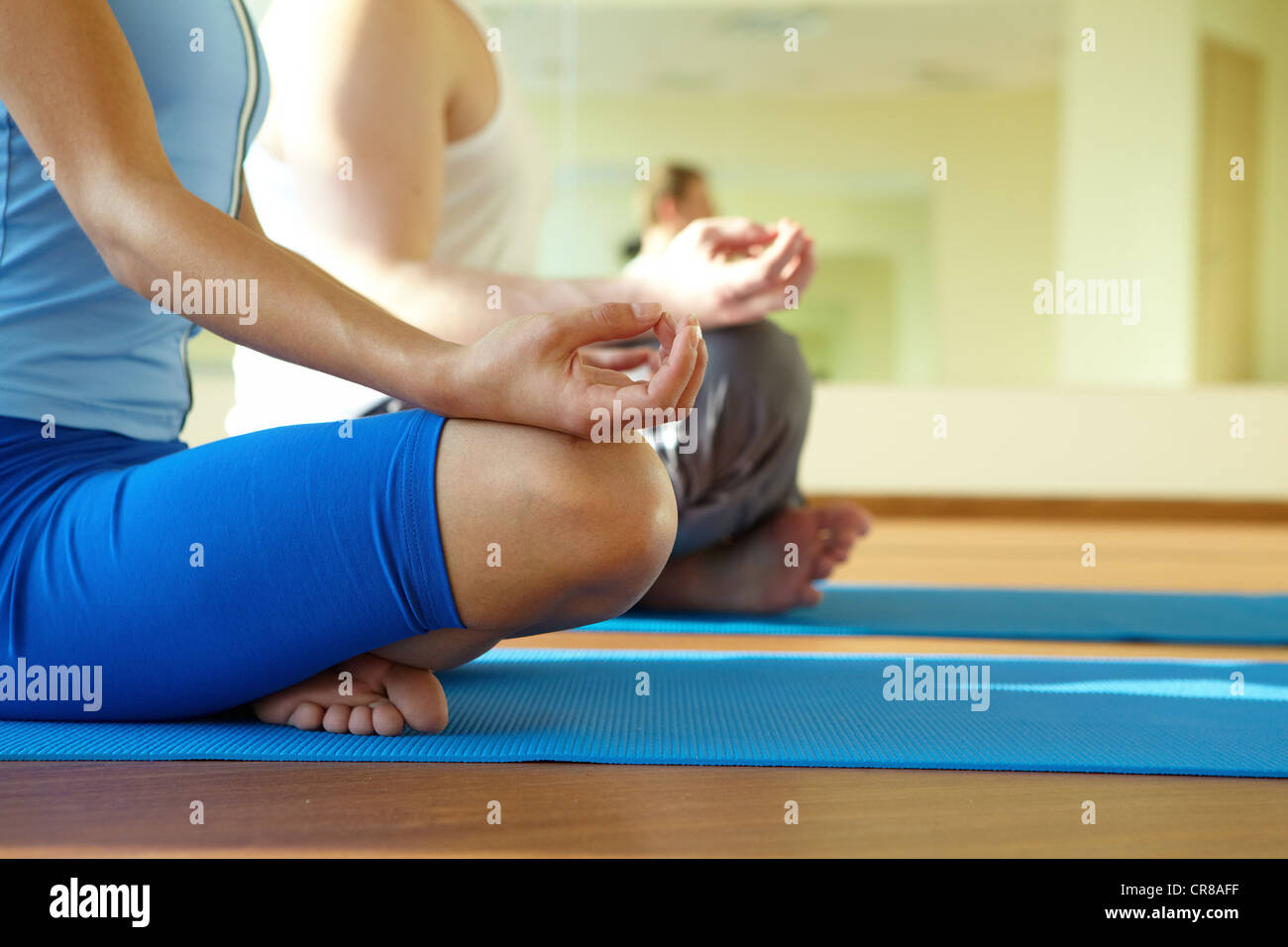 Close-up of feminine and masculine arms and crossed legs during meditation - Stock Image