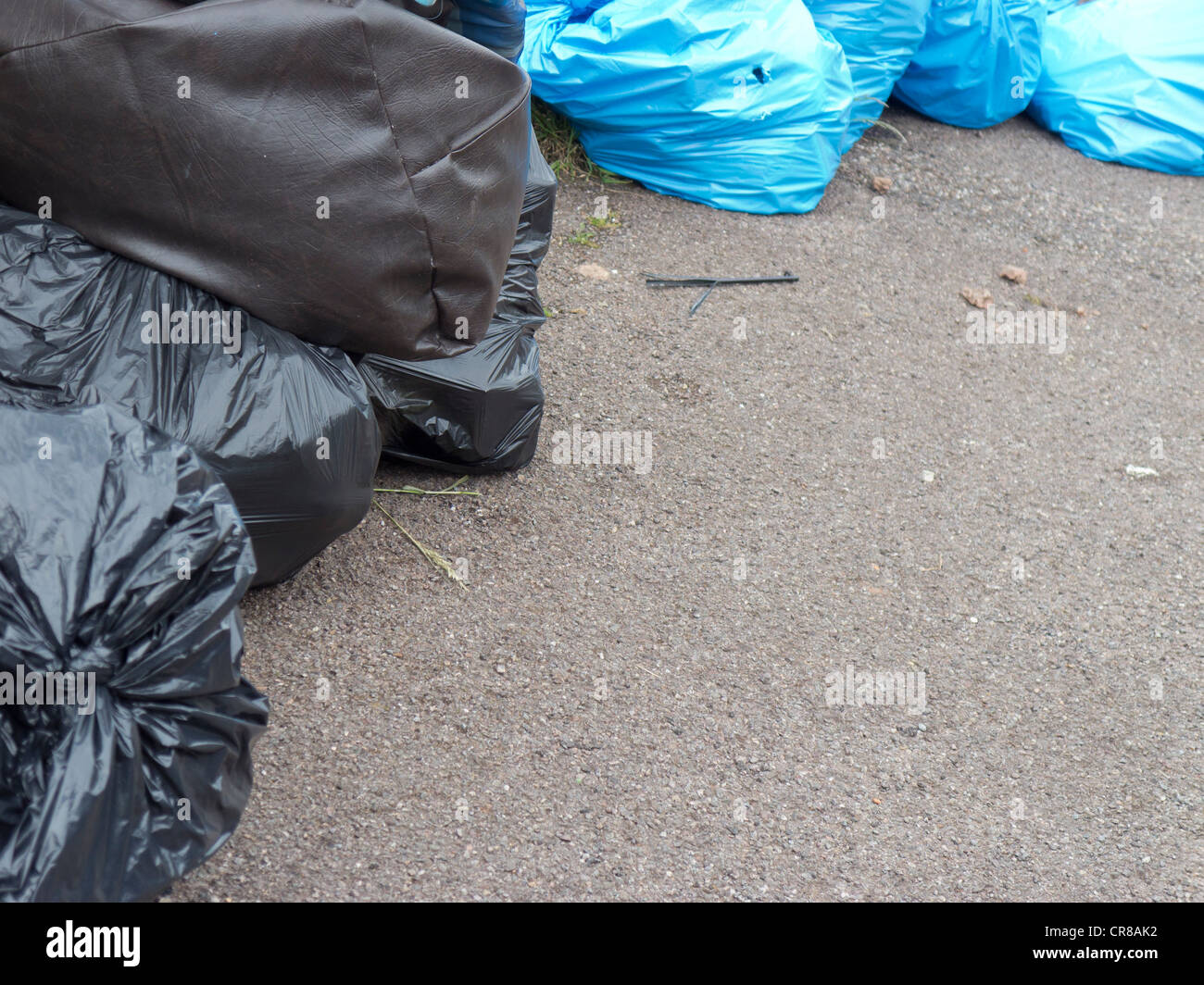 Rubbish bags await collection on the pavement. - Stock Image