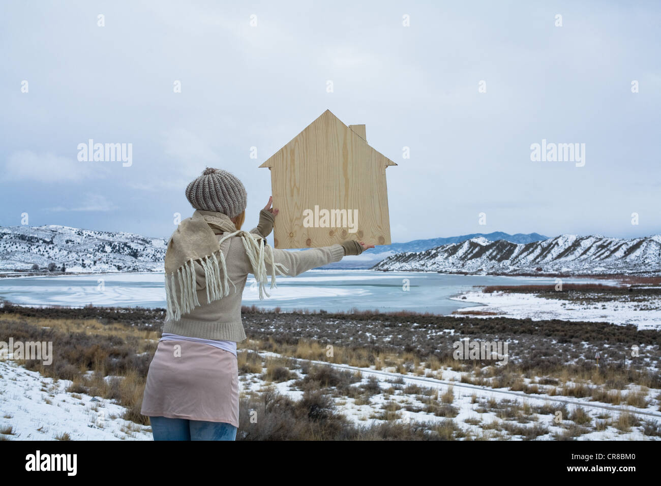 Woman in scenic landscape with wooden shape of a house - Stock Image