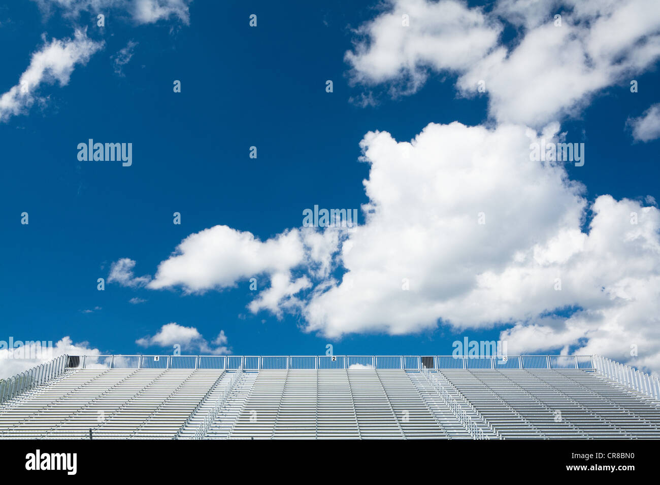Blue sky and clouds above empty stadium seats - Stock Image