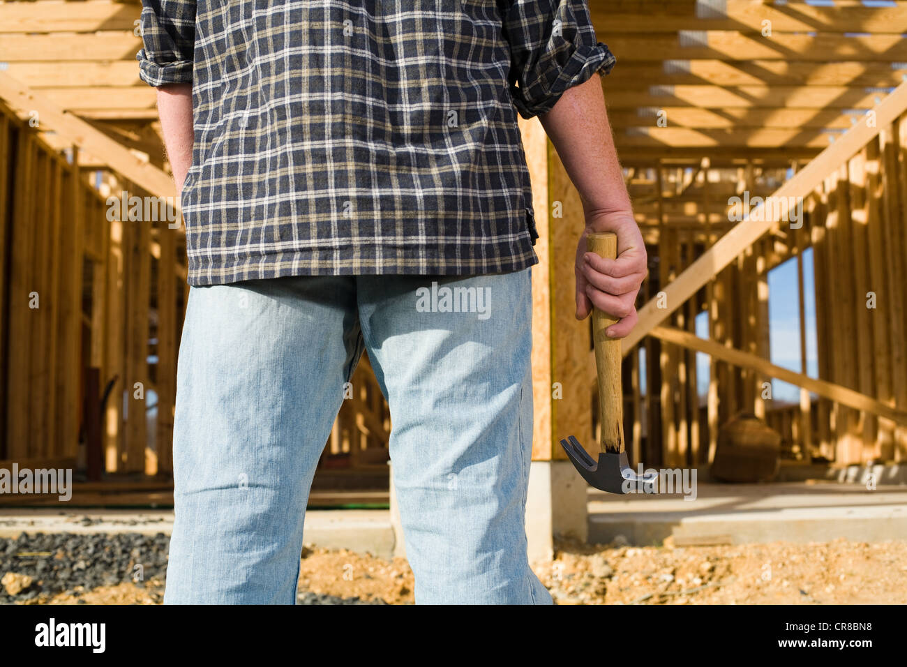 Man with hammer in front of frame of new house - Stock Image